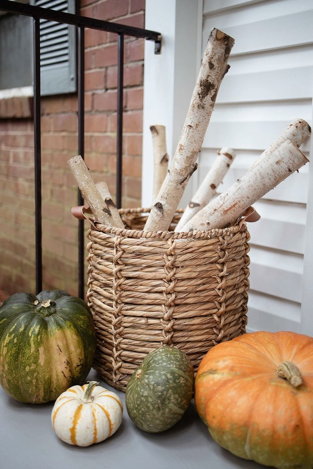 Birch logs stored inside basket with leather handles with pumpkins on floor around it