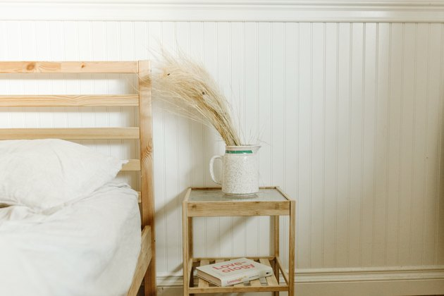 Dried grasses in a white pitcher on nightstand by bed