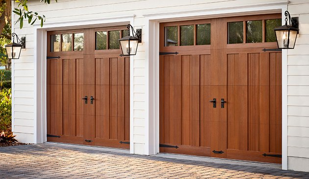 pair of wooden garage doors with paneling and windows flanked by wall sconces