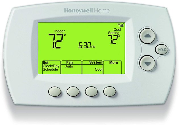 White rounded rectangular thermostat with green backlit interface