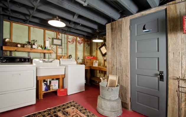 gray unfinished basement idea with red floors and laundry