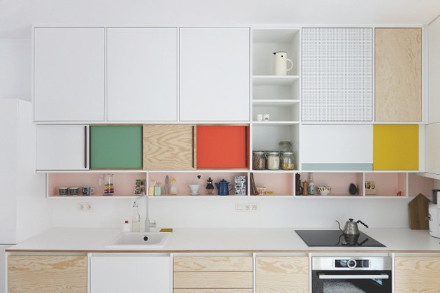Multi colored cabinets, induction stove, white counters.