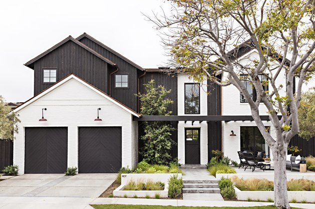 Black garage door colors on white modern farmhouse with double garage.