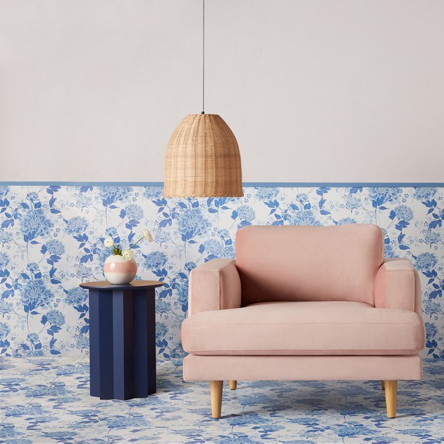 pink chair in front of blue floral wallpaper