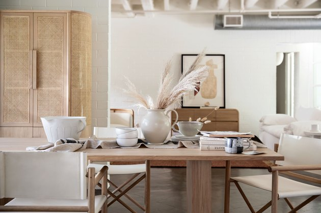 dining table with dinnerware and white furniture in the background