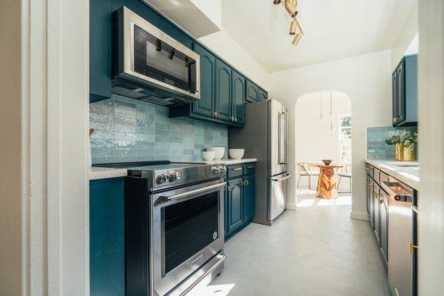 Teal cabinets, induction stove, light teal tile backsplash, microwave.