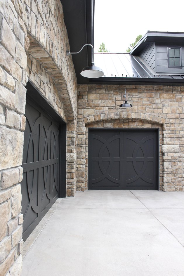 Farmhouse garage doors with black circular patterns and stone exterior
