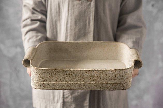 person holding ceramic bakeware, Freefolding baking dish