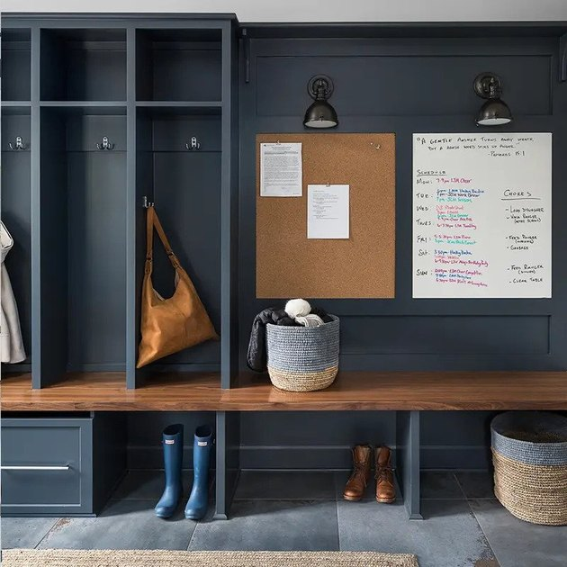 gray garage mudroom with wooden in-built bench and noticeboard