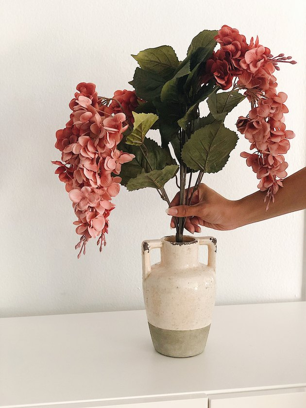 Adding faux flowers to a rustic vase.