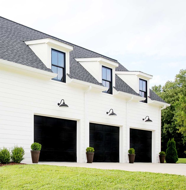 Farmhouse garage doors in black with black barn lights and white exterior