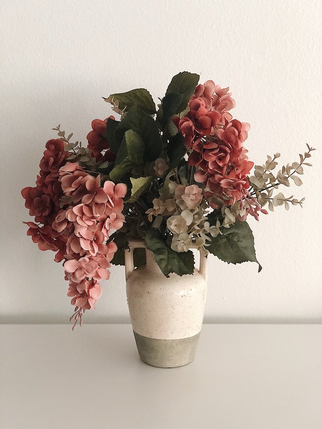 Faux flowers in a rustic vase.