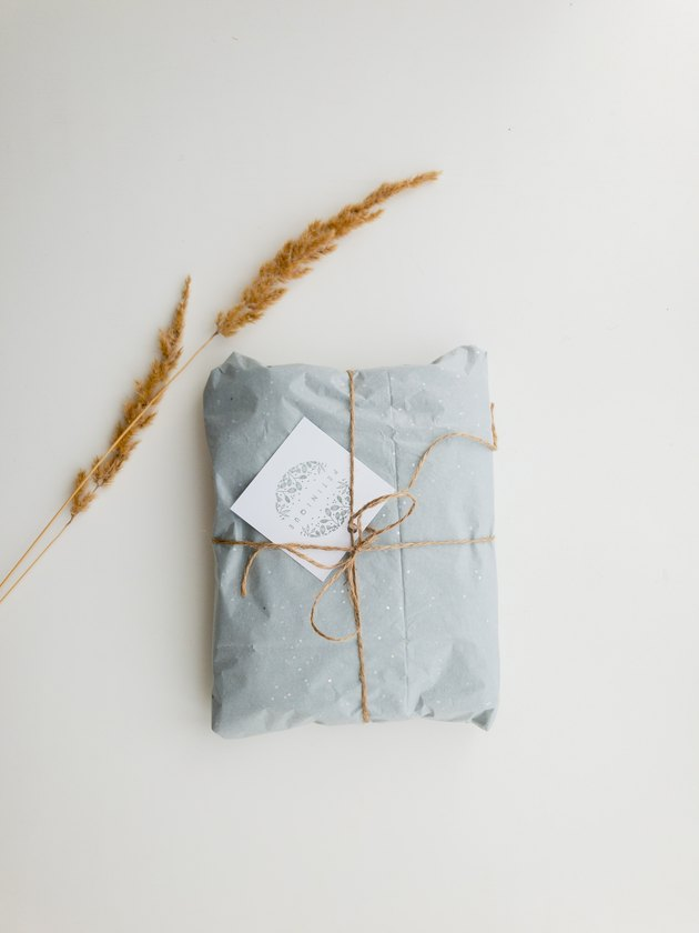 gift wrapped in brown twine with note card and wheat leaves