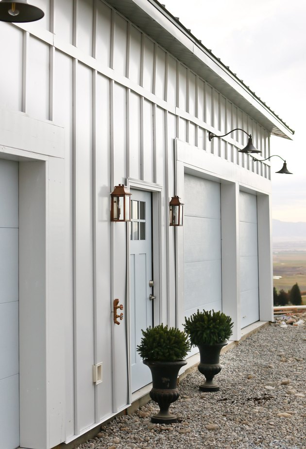 light blue farmhouse garrage doors with barn-style lighting
