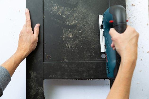 Scie sauteuse découpant un panneau noir sur une armoire IKEA