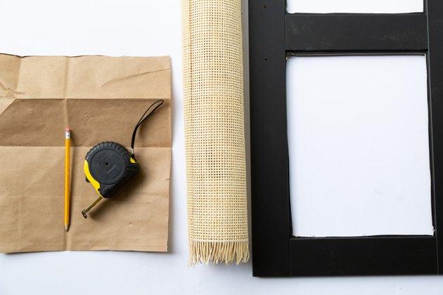 Papier brun avec crayon et ruban à mesurer, à côté de la cannage et du meuble IKEA noir