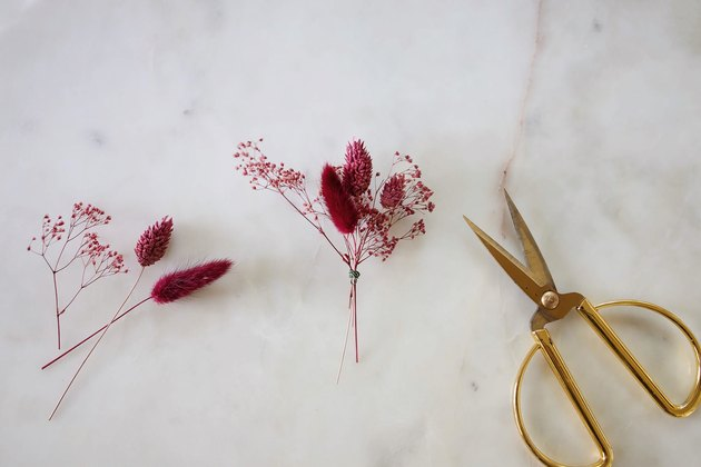 Bundling berry-colored dried flowers together with wire