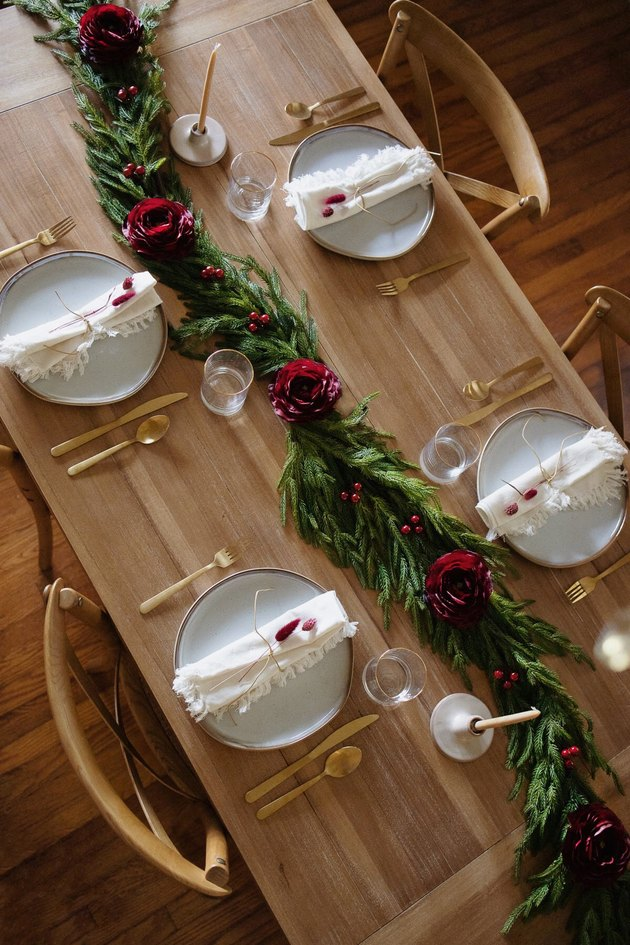 Holiday garland table runner decorated with burgundy ranunculus and berries