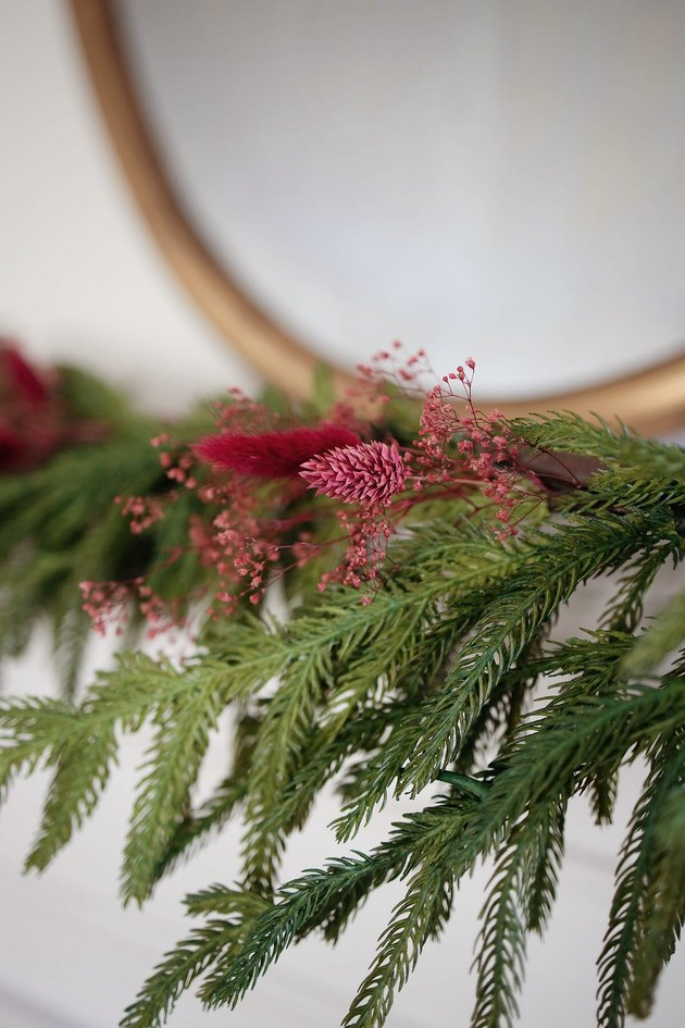 Dried berry-colored florals tucked into mantel garland