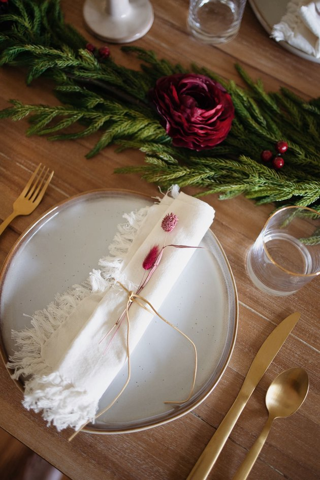 Leather cord tied around fringed napkin with burgundy bunny tail and phalaris grass tucked under it