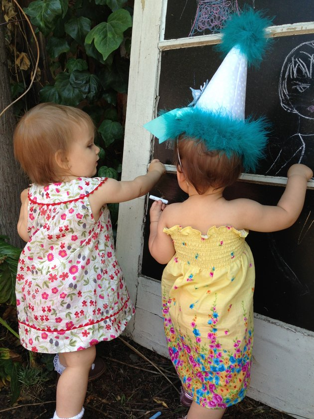 Two toddlers drawing on reclaimed door with chalkboard painted–glass panes in backyard