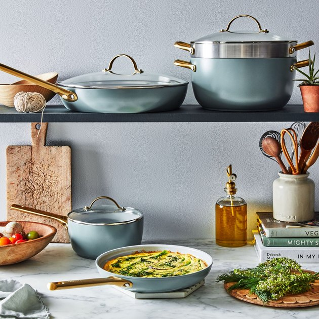 Blue ceramic nonstick cookware displayed on kitchen shelf with culinary essentials