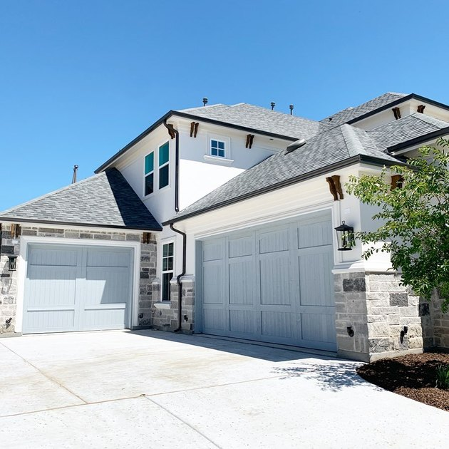 white and stone house with light blue garage doors