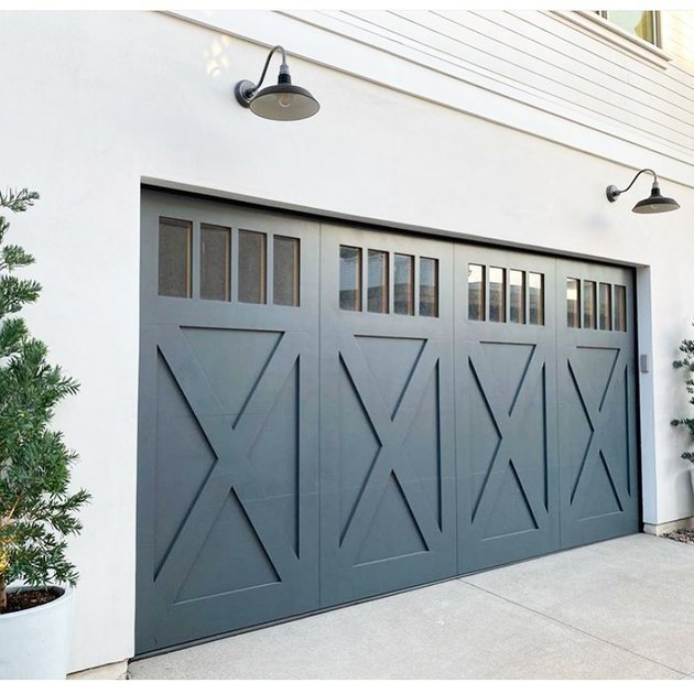 white house with farmhouse style blue garage doors