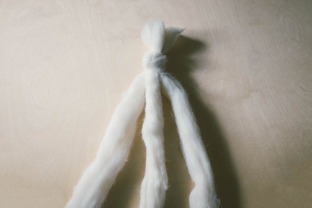 Three strands of ivory wool roving knotted together