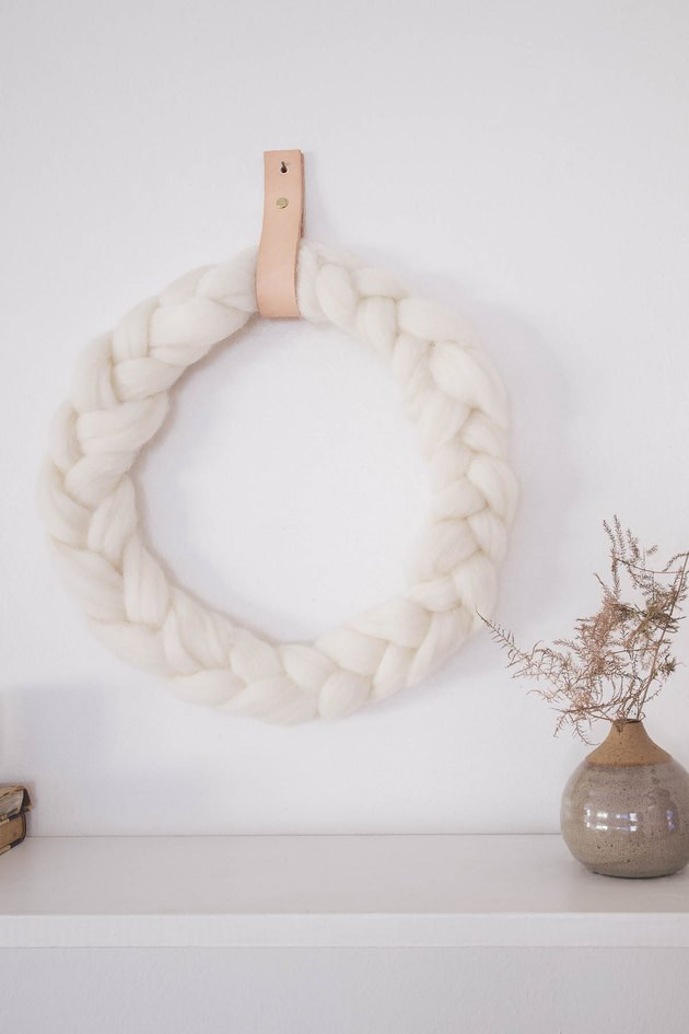 DIY braided ivory wool wreath hung on wall with leather strap
