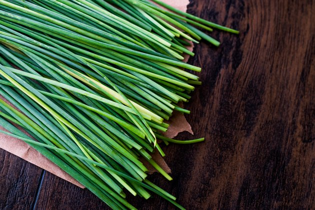 Fresh Chives / Siniklav or Frenk Sogani on wooden surface.