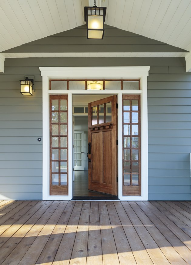 Front porch of blue-gray house with open front door