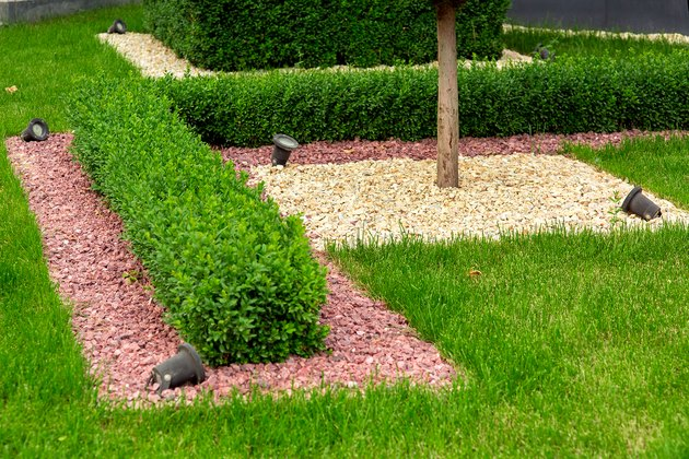 Landscape design with mulch pebbles on a lawn with boxwood bushes and a tree trunk and garden illumination lanterns, details closeup.