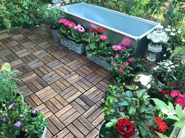 Image of garden treehouse terrace platform balcony in summer with zinc metal raised pond water feature of galvanised cattle trough ready for water, plants, fountain, red miniature roses, pink gerbera flowers, wooden decking tiles, solar lights lighting