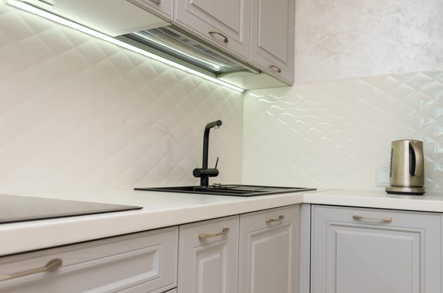 Beautiful interior of a classic kitchen in light gray and white colors with led lighting