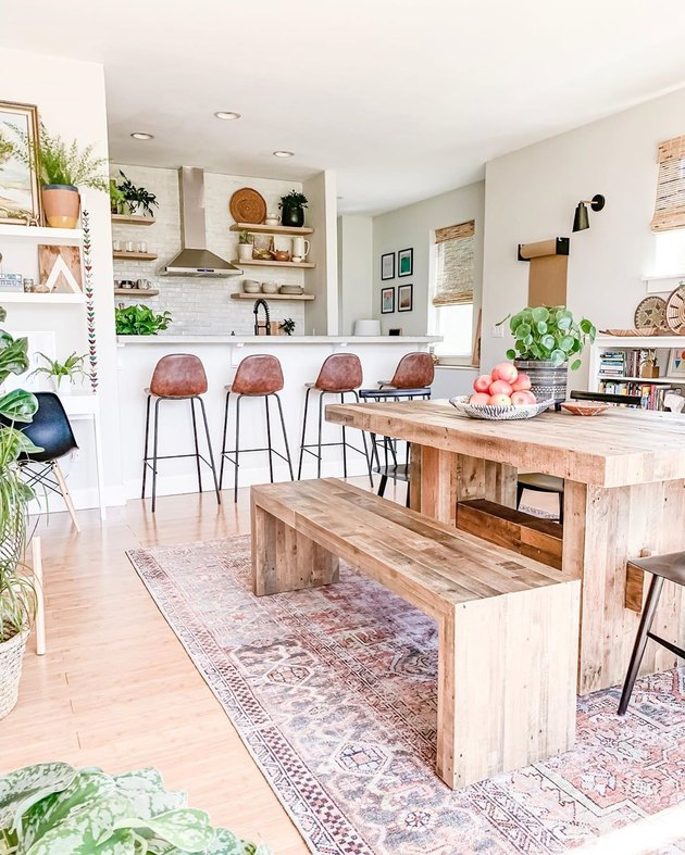 White and wood contemporary dining room with a lot of plants, natural wood dining picnic table, and minimal tan leather stools with black metal legs