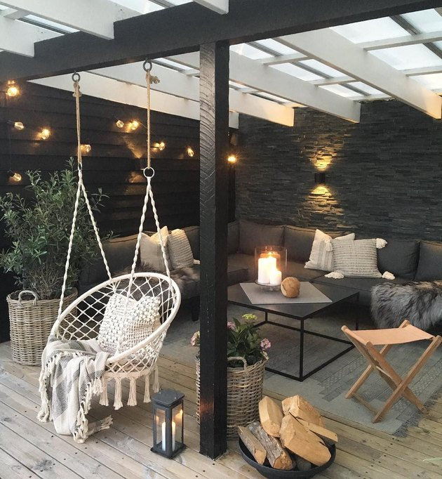 Black patio with string lights, L-shaped black couch, and hanging rope circular hammock chair