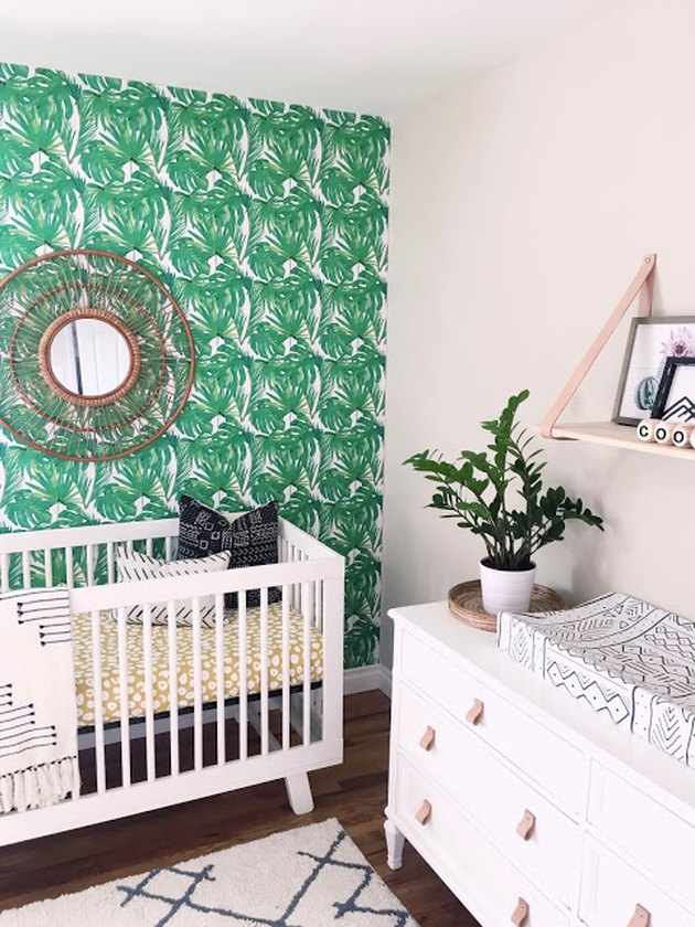 Nursery with one green leafy statement wall, sunburst mirror, and white dresser with tan leather drawer pulls