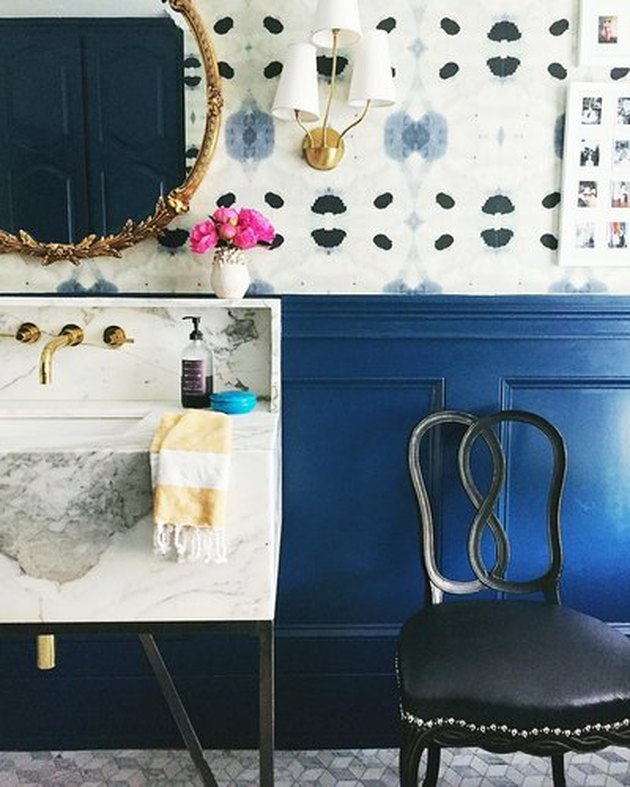 Contemporary bathroom with statement wall--top half blue and cream abstract pattern, bottom half solid blue. Round brass vintage leafy mirror and vintage bentwood chair