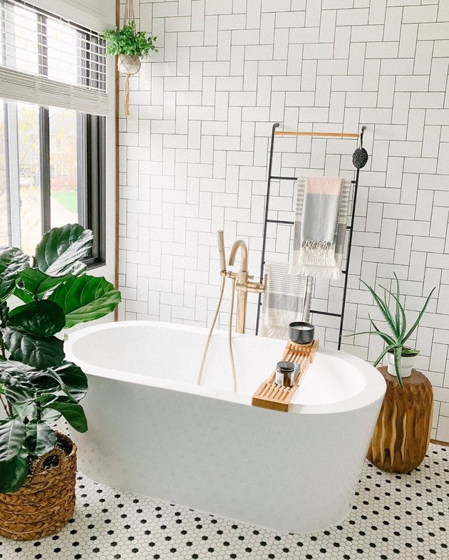 Minimal white bathroom with ladder towel rack, wooden tub caddy, and tree stump plant holder