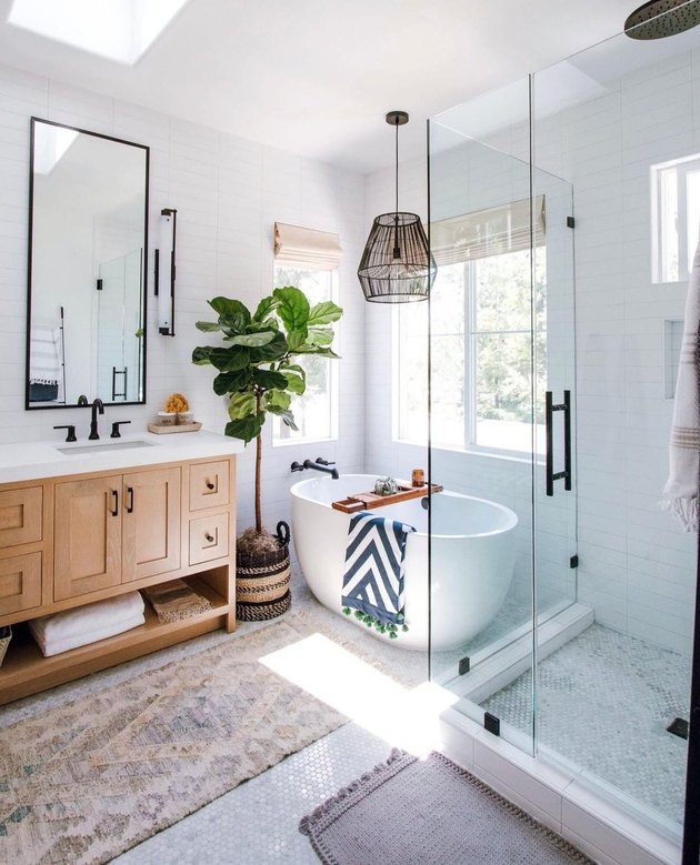 White bathroom with standalone bathtub, tall plant, wooden vanity, and black hardware