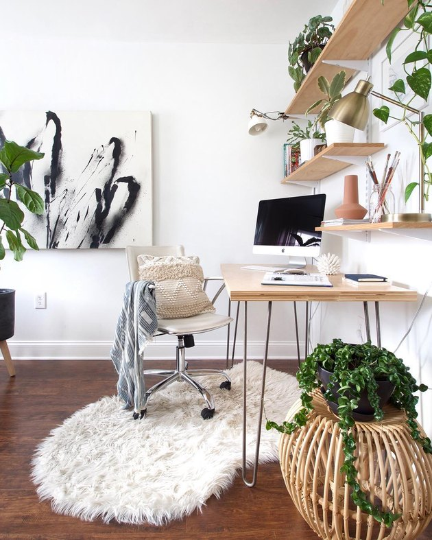 Minimal home office with blonde wood desk featuring metal hairpin legs, rolling beige swivel chair, floating wood shelves, and faux-fur white sheepskin rug