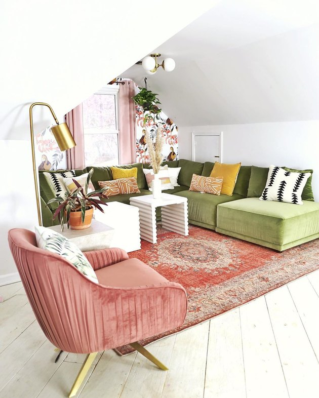 Retro attic design with olive velvet L-shaped couch and pink rug and wall mural
