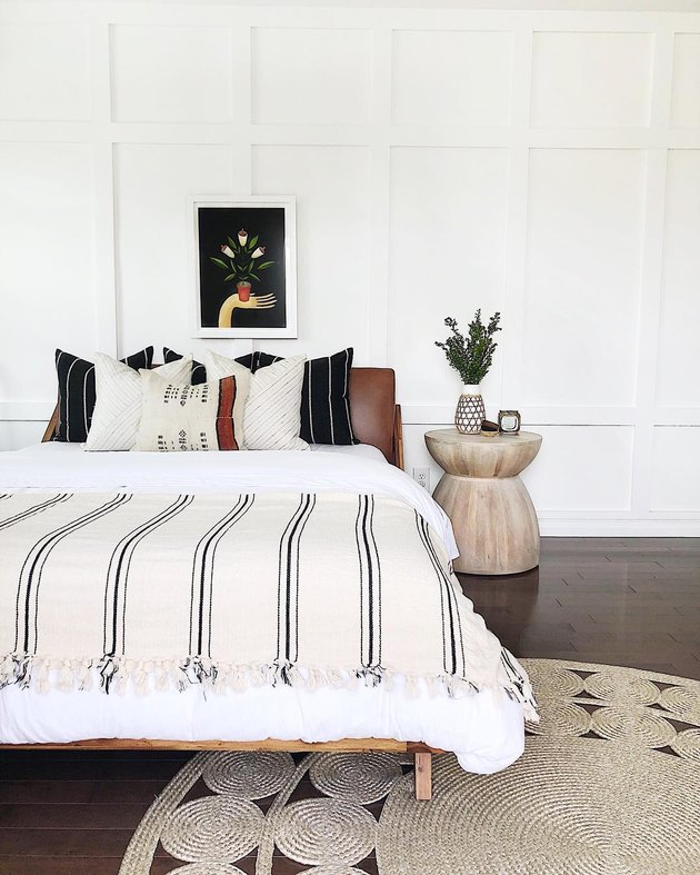 White bedroom with wood floor, wooden hourglass-shaped side table, bed with brown leather headboard and white bedding in addition to black-and-white striped throw pillows and blankets.