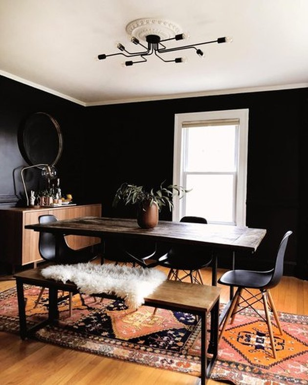 Black dining room with black midcentury dining chairs, wood and metal dining table, wood and metal bench, and black edison bulb chandelier
