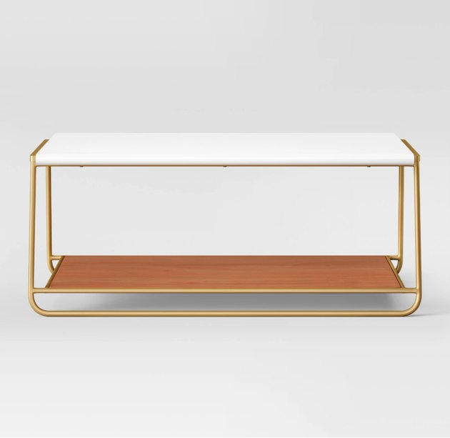 Finish off the modern aesthetic of your home decor by adding the White Coffee Table from Project 62™. This rectangular coffee table features a smooth, white top, gold legs and a light wood shelf - making it an attractive centerpiece of your living room. Place it atop a solid white rug to brighten up the space even more, or take the modern look up a notch by choosing a geometric design instead. Then, finish things off with a complementary side table and floor lamp for a room you'll love gathering friends and family in.