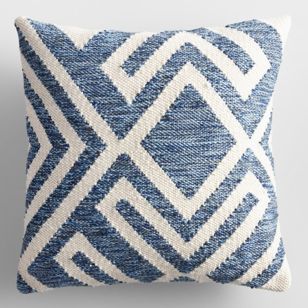 Our exclusive throw pillow features a textured blue geometric design against a cream background. Woven with thread made from recycled plastic bottles, it is appropriate for both indoor and outdoor spaces.