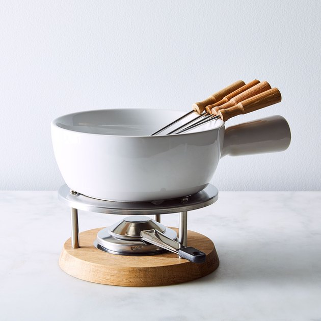Come one come all, nab a fork and gather round this fetching cheese-melting master. Bread, fruit, veggies—they're all fair game when it comes to a party where everyone can go completely dip-happy. Fully accessorized with burner, stainless steel base, and 4 fondue prongs, this oak-handled pot will take you from fromage fest to chocolate heaven in a Swiss instant.
