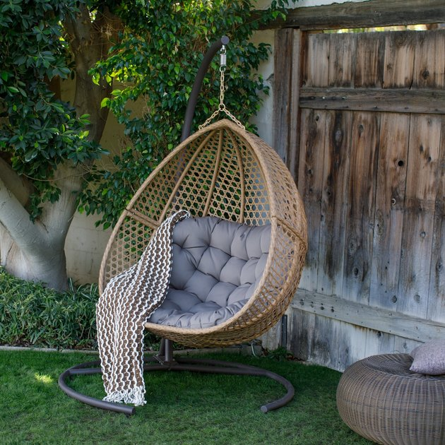 Add a touch of mid-century modern flair to your outdoor seating area with the Belham Living Cayman Resin Wicker Hanging Double Egg Chair with Cushion and Stand. Constructed from robust steel material, this sturdy frame is wrapped in weather-resistant resin wicker in a natural finish that's chip-resistant and designed to last year after year.