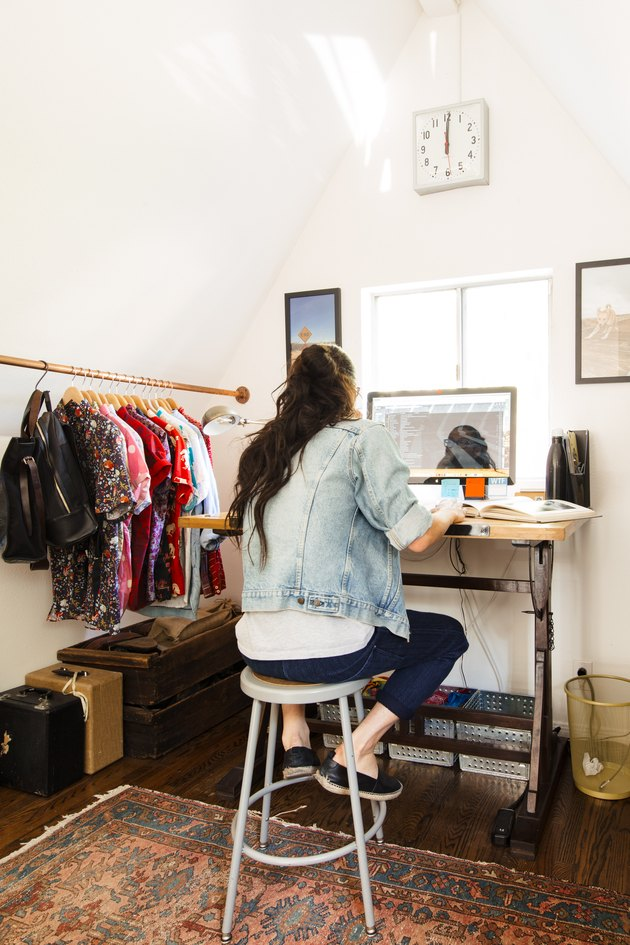 Standing desk inside a closet space with wardrobe rack, clock on wall, area rug with Home Office Desk Ideas